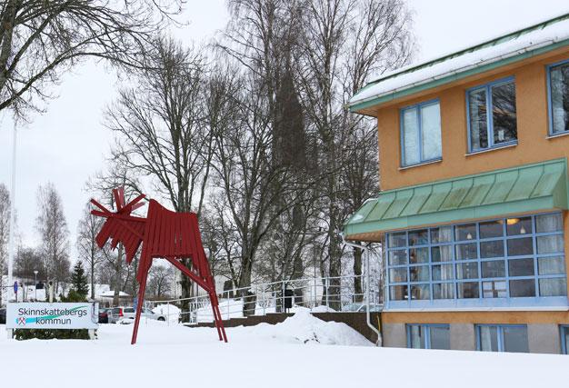 Skinnskattebergs kommunhus och kyrkan i bakgrunden.